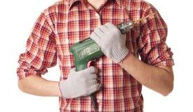 Χέρια που χειρίζονται μια ηλεκτρική μηχανή διατρήσεων Στοκ Φωτογραφίες