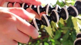 Χέρια που χρησιμοποιούν ένα gorillapod Χειριμένος ένα φορητό και εύκαμπτο μίνι τρίποδο ΣΕ ΑΡΓΗ ΚΊΝΗΣΗ απόθεμα βίντεο