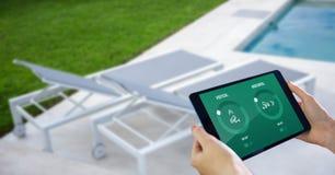 Χέρια που χρησιμοποιούν την έξυπνη εγχώρια εφαρμογή στην ψηφιακή ταμπλέτα στο poolside στοκ φωτογραφία
