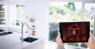 Χέρια που χρησιμοποιούν το έξυπνο σπίτι app στην κουζίνα Στοκ εικόνα με δικαίωμα ελεύθερης χρήσης