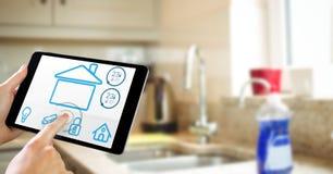 Χέρια που χρησιμοποιούν το έξυπνο σπίτι app στον υπολογιστή ταμπλετών στην κουζίνα Στοκ Εικόνες
