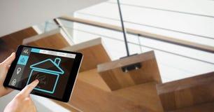 Χέρια που χρησιμοποιούν το έξυπνο σπίτι app στο PC ταμπλετών με τη σκάλα στο υπόβαθρο Στοκ Εικόνες