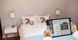 Χέρια που χρησιμοποιούν το έξυπνο σπίτι app στο PC ταμπλετών στην κρεβατοκάμαρα Στοκ Εικόνες