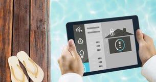 Χέρια που χρησιμοποιούν το έξυπνο σπίτι app στο poolside Στοκ Φωτογραφίες