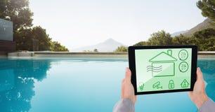 Χέρια που χρησιμοποιούν το έξυπνο σπίτι app στο poolside Στοκ φωτογραφία με δικαίωμα ελεύθερης χρήσης