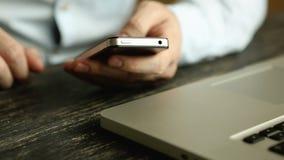 Χέρια που χρησιμοποιούν το κινητό τηλέφωνο στο ξύλινο γραφείο φιλμ μικρού μήκους