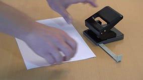 Χέρια που χρησιμοποιούν το μαύρο έγγραφο puncher απόθεμα βίντεο