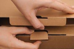 Χέρια προσώπων που ανοίγουν ένα κουτί από χαρτόνι Στοκ Φωτογραφία