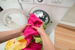 Χέρια προσώπων που βάζουν τις πετσέτες στο πλυντήριο Στοκ φωτογραφία με δικαίωμα ελεύθερης χρήσης