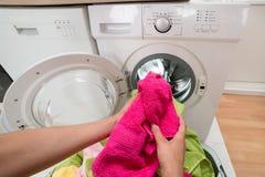 Χέρια προσώπων που βάζουν τις πετσέτες στο πλυντήριο Στοκ Φωτογραφίες