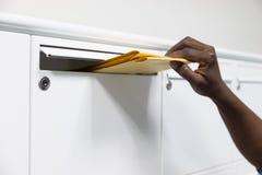Χέρια προσώπων που βάζουν το φάκελο στο ταχυδρομικό κουτί Στοκ φωτογραφία με δικαίωμα ελεύθερης χρήσης