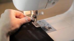 Χέρια ράβοντας μηχανών και γυναικών, μοδίστρα που υποστηρίζουν ένα ύφασμα φιλμ μικρού μήκους