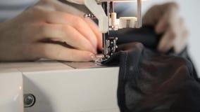 Χέρια ράβοντας μηχανών και γυναικών, μοδίστρα που υποστηρίζουν ένα ύφασμα απόθεμα βίντεο