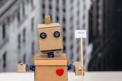 Χέρια ρομπότ που κρατούν ένα πιάτο με την επιγραφή ` γειά σου ` στοκ φωτογραφία