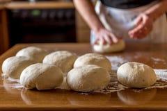 Χέρια στα κομμάτια για τη ζύμη για τις πίτσες Στοκ Εικόνα