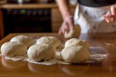 Χέρια στα κομμάτια για τη ζύμη για τις πίτσες Στοκ φωτογραφία με δικαίωμα ελεύθερης χρήσης