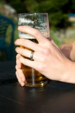 Χέρια στο ποτήρι της μπύρας Στοκ φωτογραφία με δικαίωμα ελεύθερης χρήσης