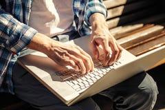 Χέρια στο lap-top στοκ εικόνες