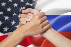 Χέρια συνεργασίας με τις αμερικανικές και ρωσικές σημαίες Στοκ εικόνα με δικαίωμα ελεύθερης χρήσης