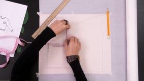 Χέρια σχεδιαστών που χρωματίζουν ένα σχέδιο για το ράψιμο της μπλούζας r φιλμ μικρού μήκους