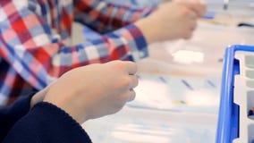 Χέρια σχολικών αγοριών στην τάξη εφαρμοσμένης μηχανικής που κάνει το ρομπότ Εκπαίδευση Robotechnics φιλμ μικρού μήκους