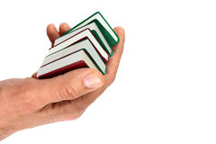 Χέρια τα μικρά μικροσκοπικά βιβλία, που απομονώνονται που κρατούν στο λευκό Στοκ Εικόνες