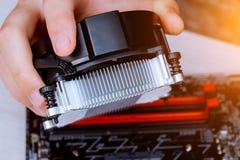 Χέρια τεχνικών που εγκαθιστούν τον πιό δροσερό ανεμιστήρα ΚΜΕ σε μια μητρική κάρτα PC υπολογιστών στοκ εικόνα