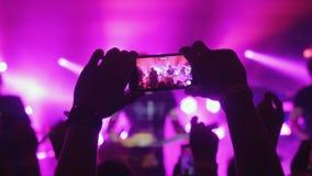 Χέρια της γυναίκας ανεμιστήρων που καταγράφουν το βίντεο με τα έξυπνα τηλέφωνα στη συναυλία βράχου στα ρόδινα χρώματα Στοκ Φωτογραφία