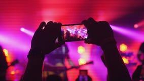 Χέρια της γυναίκας ανεμιστήρων που καταγράφουν το βίντεο με τα έξυπνα τηλέφωνα στη συναυλία βράχου στα κόκκινα χρώματα υποβάθρου στοκ εικόνα