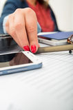 Χέρια της γυναίκας γραφείων κινηματογραφήσεων σε πρώτο πλάνο που παίρνουν penfrom το άσπρο γραφείο με κινητό, τα γυαλιά και το πλ Στοκ εικόνα με δικαίωμα ελεύθερης χρήσης