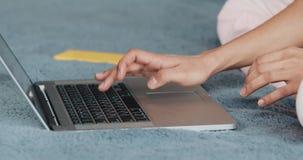 Χέρια της γυναίκας κινηματογραφήσεων σε πρώτο πλάνο που χρησιμοποιούν το lap-top στο κρεβάτι Κοριτσιών στο φορητό προσωπικό υπολο απόθεμα βίντεο