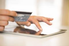Χέρια της γυναίκας κινηματογραφήσεων σε πρώτο πλάνο που κρατούν μια πιστωτική κάρτα και που χρησιμοποιούν το PC ταμπλετών Στοκ Φωτογραφία