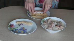 Χέρια της γυναίκας οι πασπαλίζοντας με ψίχουλα ακατέργαστες λωρίδες από την κινηματογράφηση σε πρώτο πλάνο στηθών κοτόπουλου φιλμ μικρού μήκους