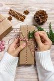 Χέρια της γυναίκας που διακοσμεί το κιβώτιο δώρων Χριστουγέννων Χέρια της γυναίκας που διακοσμεί το κιβώτιο δώρων Χριστουγέννων Στοκ φωτογραφία με δικαίωμα ελεύθερης χρήσης