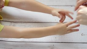 Χέρια της κινηματογράφησης σε πρώτο πλάνο χεριών παιδιών και μητέρων ` s, στα πλαίσια ενός ξύλινου πίνακα, σε έναν επιβραδυνμένο  φιλμ μικρού μήκους