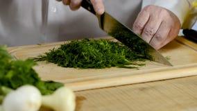 Χέρια της μεγάλης κουζίνας μαχαιριών μαγείρων ένα φρέσκο πράσινο μάραθο σε έναν τεμαχίζοντας πίνακα από ένα δέντρο φιλμ μικρού μήκους
