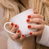 Χέρια της νέας γυναίκας με την κόκκινη στιλβωτική ουσία καρφιών που κρατά ένα άσπρο φλυτζάνι Στοκ Εικόνες