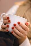 Χέρια της νέας γυναίκας με την κόκκινη στιλβωτική ουσία καρφιών που κρατά ένα άσπρο φλυτζάνι Στοκ εικόνα με δικαίωμα ελεύθερης χρήσης