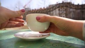 Χέρια της νέας γυναίκας που παίρνουν ένα άσπρο φλιτζάνι του καφέ ή ένα cappuccino από τον πίνακα στο εστιατόριο έξω φιλμ μικρού μήκους