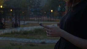 Χέρια της νέας δακτυλογράφησης γυναικών στο κινητό τηλέφωνο απόθεμα βίντεο