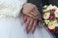 Χέρια της νύφης και του νεόνυμφου με τα γαμήλια δαχτυλίδια, το ζεύγος Στοκ εικόνα με δικαίωμα ελεύθερης χρήσης