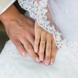 Χέρια της νύφης και του νεόνυμφου με τα γαμήλια δαχτυλίδια Στοκ εικόνες με δικαίωμα ελεύθερης χρήσης