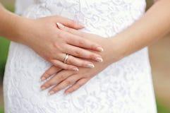 Χέρια της νύφης με μια κινηματογράφηση σε πρώτο πλάνο δαχτυλιδιών και μανικιούρ Στοκ φωτογραφία με δικαίωμα ελεύθερης χρήσης