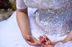 Χέρια της νύφης σε ένα άσπρο φόρεμα με το κόκκινο μανικιούρ Στοκ Εικόνες