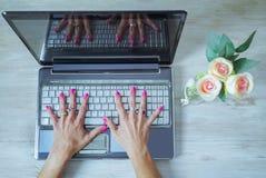 χέρια της όμορφης γυναίκας με τα χρωματισμένα καρφιά ανοικτά σε ένα πληκτρολόγιο υπολογιστών στοκ φωτογραφίες