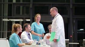 Χέρια τινάγματος γιατρών και αλληλεπίδραση με τους συναδέλφους στη αίθουσα συνδιαλέξεων απόθεμα βίντεο