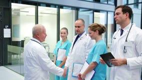 Χέρια τινάγματος γιατρών και αλληλεπίδραση με τους συναδέλφους στο διάδρομο απόθεμα βίντεο