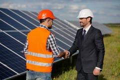 Χέρια τινάγματος επιχειρηματιών και επιστατών στο σταθμό ηλιακής ενέργειας Στοκ εικόνα με δικαίωμα ελεύθερης χρήσης