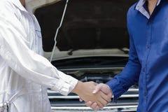Χέρια τινάγματος μηχανικών και πελατών μετά από τη μηχανή επισκευής του αυτοκινήτου στο αυτόματο γκαράζ υπηρεσιών Στοκ Φωτογραφία