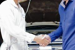 Χέρια τινάγματος μηχανικών και πελατών μετά από τη μηχανή επισκευής στο αυτόματο γκαράζ υπηρεσιών Πώληση αυτοκινήτων ή έννοια δια Στοκ Φωτογραφία